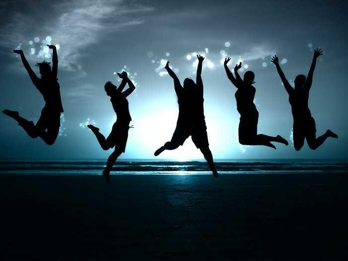 Люди в прыжке на фоне моря