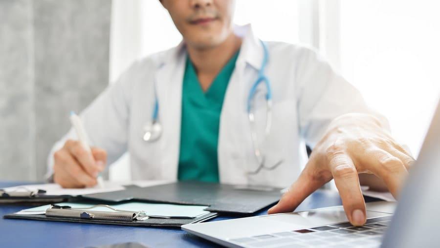 Врач пишет в карточке пациента